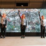 Three young woman stand in front of a map of Manchester on a wall of TV screens, their fists are raised in the air in performance of Ling Tan's SUPERGESTURES