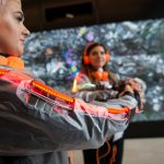 Three young woman in wearable technology with light strips and headphones perform SUPERGESTURES in front of a large digital map of Manchester at the Bright Building during Future Sessions
