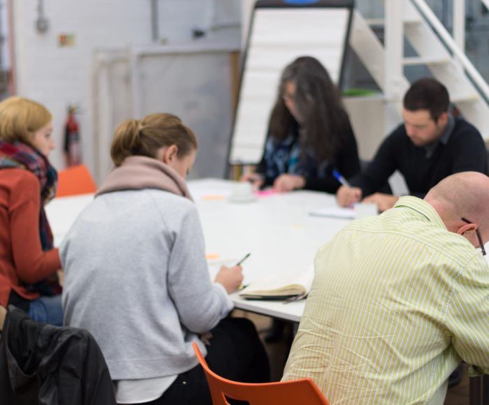 Group of people writing ideas during a knowledge sharing workshop