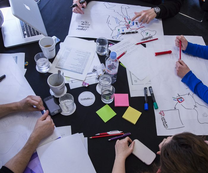 A group of people drawing maps and ideas as part of a participatory design workshop