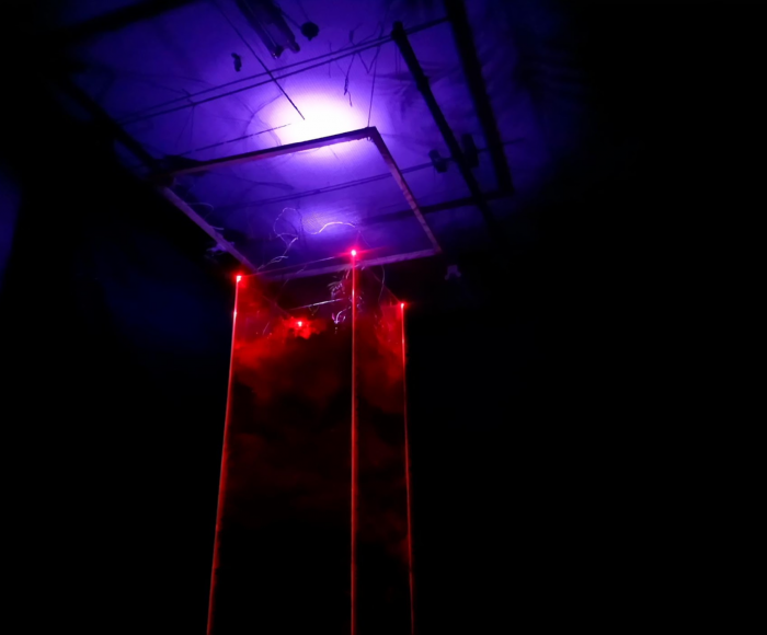 A very tall glass wormery is lit up with red and purple lights in a darkened room