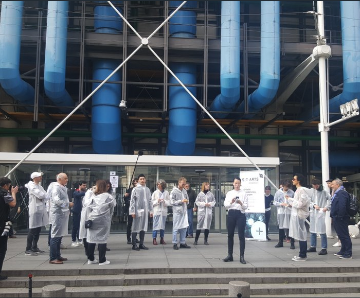 a group of people in lab coats gather outside the Pompidou Centre for Ling Tan's Pollution Explorers
