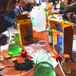 A group of people sit around a long table, all looking at a woman speaking and holding a laptop. A science jar full of green liquid is on the table