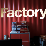 Red stacked boxes appear in front of a red metal wall, above in gold is the word 'Factory'