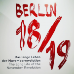 The words Berlin 18/19 are printed in red on a white background. Below typed in black font is: The Long Life of the November Revolution