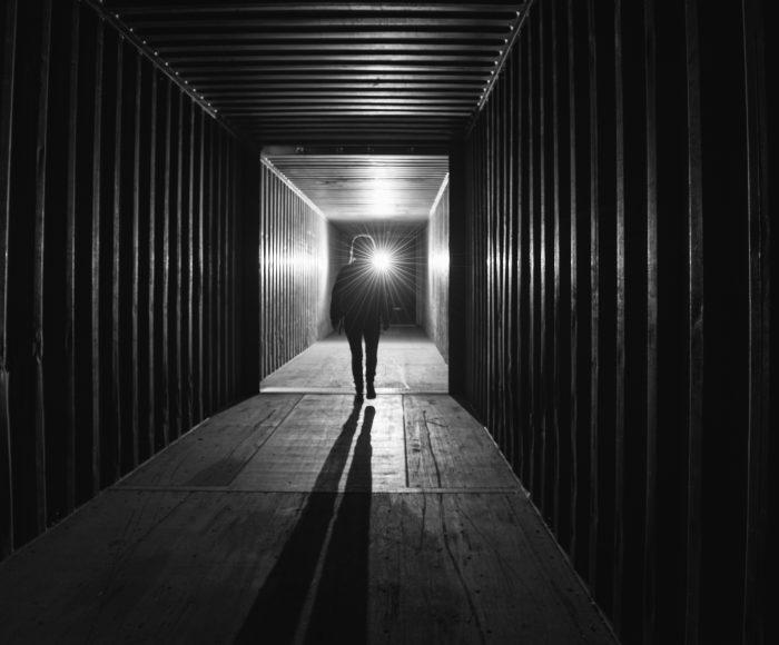 woman walking into dark tunnel