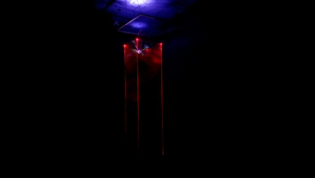 A perspex column in the dark, with a light above it and soil inside
