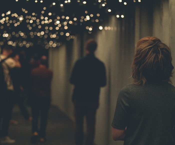 A group of people walk through a dimly lit corridor where tiny speakers with lights line the roof
