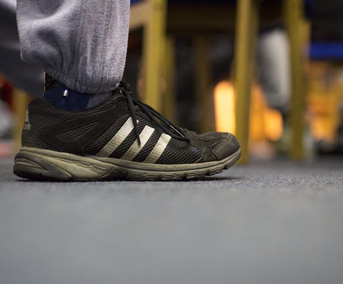 A man's foot placed on a grey carpet, he is wearing grey jogging pants and black adidas trainers covered in mud