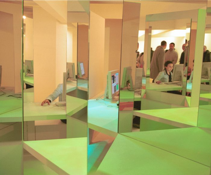 A hall of reflective mirrors showing relflections of four or five people