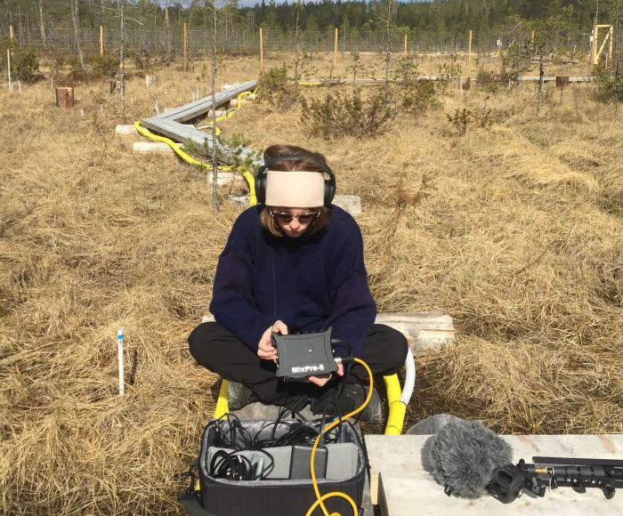 A woman sits in a field wearing headphones and holding audio recording equipment